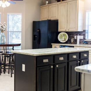 Cette image montre une cuisine américaine parallèle style shabby chic de taille moyenne avec un évier 2 bacs, un placard avec porte à panneau encastré, des portes de placard en bois vieilli, un plan de travail en granite, une crédence grise, une crédence en carreau de verre, un électroménager en acier inoxydable, un sol en travertin et un îlot central.