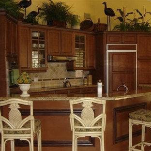 Kleine Tropische Wohnküche mit Unterbauwaschbecken, Glasfronten, gelben Schränken, Granit-Arbeitsplatte, Küchenrückwand in Beige, Rückwand aus Steinfliesen, Elektrogeräten mit Frontblende, Travertin und Halbinsel in Miami