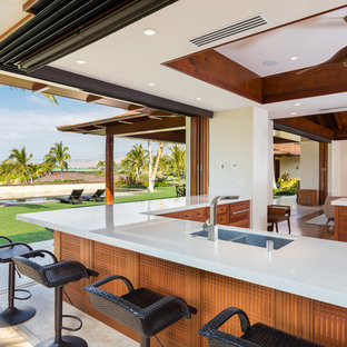 Inspiration for a large tropical l-shaped open plan kitchen in Hawaii with a double-bowl sink, recessed-panel cabinets, medium wood cabinets, quartz benchtops, stainless steel appliances, limestone floors and a peninsula.