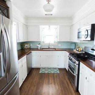ヒューストンの中くらいのビーチスタイルのおしゃれなダイニングキッチン (シングルシンク、フラットパネル扉のキャビネット、白いキャビネット、木材カウンター、青いキッチンパネル、セラミックタイルのキッチンパネル、シルバーの調理設備、クッションフロア、アイランドなし) の写真