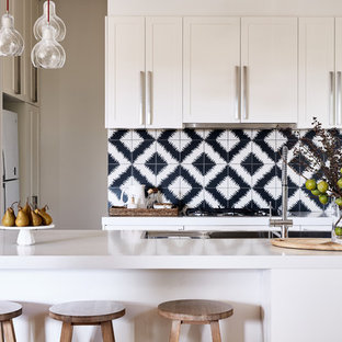 This is an example of a transitional l-shaped kitchen in Melbourne with a double-bowl sink, shaker cabinets, white cabinets, quartz benchtops, cement tile splashback, stainless steel appliances, light hardwood floors, an island, white benchtop and black splashback.