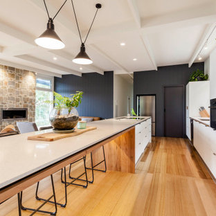 Photo of a contemporary galley kitchen in Melbourne with an undermount sink, flat-panel cabinets, white cabinets, black appliances, medium hardwood floors, with island and brown floor.