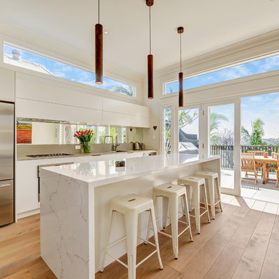 Inspiration for a large contemporary galley brown floor and medium tone wood floor open concept kitchen remodel in Sydney with a drop-in sink, white cabinets, quartz countertops, mirror backsplash, stainless steel appliances, an island, flat-panel cabinets, metallic backsplash and white countertops
