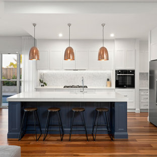 Inspiration for a large transitional l-shaped kitchen in Brisbane with a farmhouse sink, shaker cabinets, quartz benchtops, multi-coloured splashback, ceramic splashback, medium hardwood floors, with island, brown floor, white benchtop, white cabinets and stainless steel appliances.