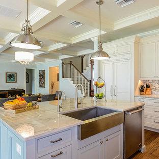 Mittelgroße Klassische Wohnküche in L-Form mit Landhausspüle, Kassettenfronten, grauen Schränken, Arbeitsplatte aus Terrazzo, Küchenrückwand in Beige, Rückwand aus Glasfliesen, Elektrogeräten mit Frontblende, hellem Holzboden und Kücheninsel in Orlando