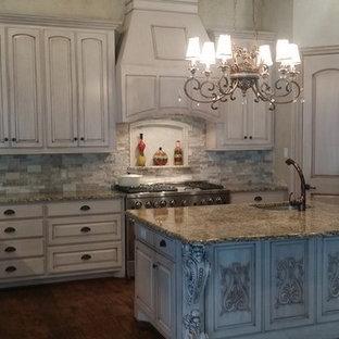 ダラスの大きいヴィクトリアン調のおしゃれなキッチン (レイズドパネル扉のキャビネット、御影石カウンター、ベージュキッチンパネル、シルバーの調理設備の、濃色無垢フローリング、茶色い床、アンダーカウンターシンク、ベージュのキャビネット、石タイルのキッチンパネル、マルチカラーのキッチンカウンター) の写真