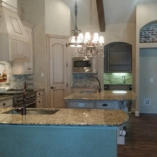 Photo of a large victorian u-shaped kitchen/diner in Dallas with raised-panel cabinets, granite worktops, beige splashback, stainless steel appliances, dark hardwood flooring, an island, brown floors, a submerged sink, beige cabinets, stone tiled splashback and multicoloured worktops.
