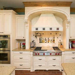 Ejemplo de cocina tradicional con armarios con paneles con relieve, puertas de armario beige, salpicadero beige y electrodomésticos de acero inoxidable