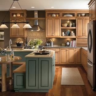 グランドラピッズの中くらいのエクレクティックスタイルのおしゃれなキッチン (アンダーカウンターシンク、インセット扉のキャビネット、クオーツストーンカウンター、ベージュキッチンパネル、セラミックタイルのキッチンパネル、シルバーの調理設備、無垢フローリング、淡色木目調キャビネット) の写真