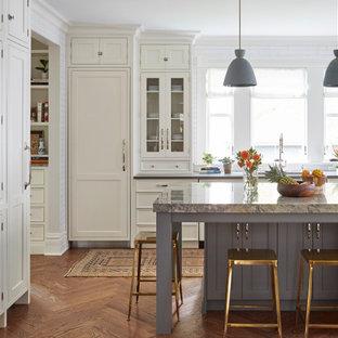 Ejemplo de cocina en L, tradicional renovada, con fregadero bajoencimera, armarios con paneles empotrados, puertas de armario blancas, electrodomésticos con paneles, suelo de madera en tonos medios, una isla, suelo marrón y encimeras grises