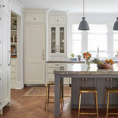 Example of a transitional l-shaped medium tone wood floor and brown floor kitchen design in Chicago with an undermount sink, recessed-panel cabinets, white cabinets, paneled appliances, an island and gray countertops