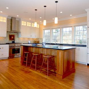ポートランド(メイン)の大きいコンテンポラリースタイルのおしゃれなキッチン (一体型シンク、フラットパネル扉のキャビネット、白いキャビネット、コンクリートカウンター、白い調理設備、無垢フローリング、茶色い床、黒いキッチンカウンター) の写真