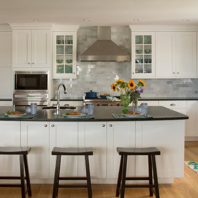Open concept kitchen - mid-sized traditional l-shaped open concept kitchen idea in Boston with shaker cabinets, white cabinets, gray backsplash, stainless steel appliances, an island, an undermount sink, granite countertops and marble backsplash