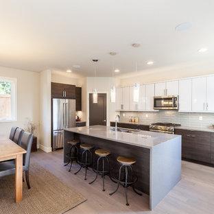 Große Moderne Wohnküche in L-Form mit Unterbauwaschbecken, flächenbündigen Schrankfronten, weißen Schränken, Küchenrückwand in Grau, Rückwand aus Glasfliesen, Küchengeräten aus Edelstahl, Vinylboden, Kücheninsel und Arbeitsplatte aus Terrazzo in Seattle
