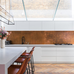 Contemporary single-wall kitchen/diner in London with flat-panel cabinets, white cabinets, light hardwood flooring, an island and metallic splashback.