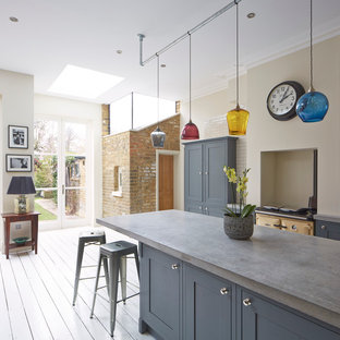 Large transitional kitchen in London with shaker cabinets, blue cabinets, concrete benchtops, beige splashback, subway tile splashback and painted wood floors.