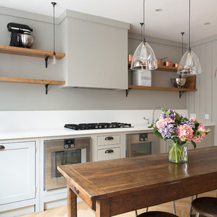 Photo of a small traditional kitchen in London with shaker cabinets, light wood cabinets and medium hardwood flooring.