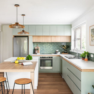 This is an example of a contemporary l-shaped kitchen in Hobart with a drop-in sink, flat-panel cabinets, green cabinets, green splashback, subway tile splashback, stainless steel appliances, medium hardwood floors, with island, brown floor and white benchtop.