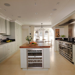 Mid-sized elegant galley limestone floor and beige floor eat-in kitchen photo in London with raised-panel cabinets, green cabinets, an integrated sink, granite countertops, stainless steel appliances, an island and black countertops