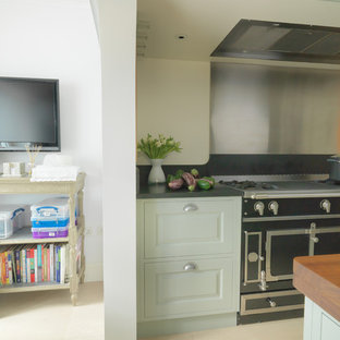 Design ideas for a mid-sized contemporary galley eat-in kitchen in London with an integrated sink, raised-panel cabinets, green cabinets, stainless steel appliances, limestone floors, with island, granite benchtops, metallic splashback, white floor and black benchtop.