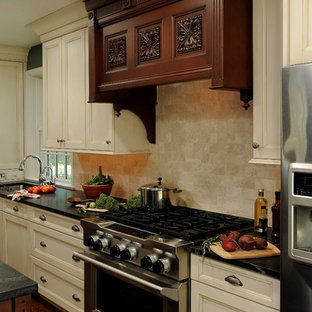 Design ideas for a mid-sized traditional u-shaped eat-in kitchen in DC Metro with an undermount sink, beaded inset cabinets, white cabinets, soapstone benchtops, beige splashback, stone tile splashback, stainless steel appliances, dark hardwood floors, multiple islands and brown floor.