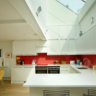 Contemporary open concept kitchen inspiration - Example of a trendy u-shaped light wood floor open concept kitchen design in London with an undermount sink, flat-panel cabinets, white cabinets, red backsplash, black appliances and a peninsula