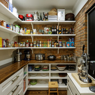 Traditional kitchen pantry ideas - Kitchen pantry - traditional l-shaped dark wood floor and brown floor kitchen pantry idea in Cincinnati with white cabinets, wood countertops, brick backsplash and brown countertops