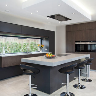 Medium sized contemporary l-shaped kitchen/diner in Belfast with a double-bowl sink, flat-panel cabinets, black cabinets, quartz worktops, black appliances, an island, white floors and white worktops.