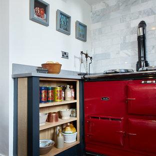 他の地域の中サイズのコンテンポラリースタイルのおしゃれなキッチン (エプロンフロントシンク、フラットパネル扉のキャビネット、淡色木目調キャビネット、御影石カウンター、グレーのキッチンパネル、石スラブのキッチンパネル、カラー調理設備、セメントタイルの床、黒い床、グレーのキッチンカウンター) の写真