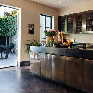 Idéer för att renovera ett funkis kök, med luckor med glaspanel, bruna skåp, beige stänkskydd, mörkt trägolv, en köksö och brunt golv