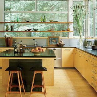 ニューヨークのコンテンポラリースタイルのおしゃれなキッチン (フラットパネル扉のキャビネット、淡色木目調キャビネット、ガラスまたは窓のキッチンパネル、シルバーの調理設備の、淡色無垢フローリング、ベージュの床、黒いキッチンカウンター) の写真