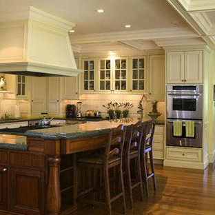 This is an example of a large traditional l-shaped separate kitchen in San Francisco with beaded inset cabinets, beige cabinets, granite benchtops, beige splashback, stainless steel appliances, bamboo floors and with island.