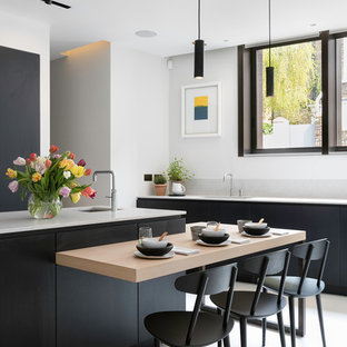 Large contemporary l-shaped kitchen/diner in London with a submerged sink, flat-panel cabinets, black cabinets, marble worktops, multi-coloured splashback, marble splashback, black appliances, ceramic flooring, beige floors and multiple islands.