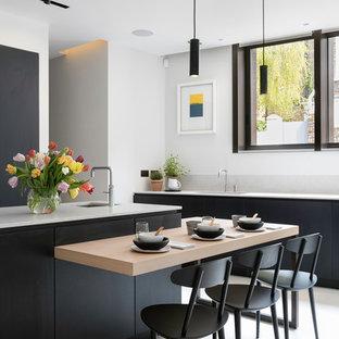 ロンドンの大きいコンテンポラリースタイルのおしゃれなキッチン (アンダーカウンターシンク、フラットパネル扉のキャビネット、黒いキャビネット、大理石カウンター、マルチカラーのキッチンパネル、大理石の床、黒い調理設備、セラミックタイルの床、ベージュの床) の写真