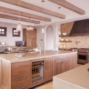 サンフランシスコの中サイズのインダストリアルスタイルのおしゃれなキッチン (エプロンフロントシンク、シェーカースタイル扉のキャビネット、濃色木目調キャビネット、ステンレスカウンター、ベージュキッチンパネル、レンガのキッチンパネル、シルバーの調理設備の、淡色無垢フローリング、ベージュの床) の写真