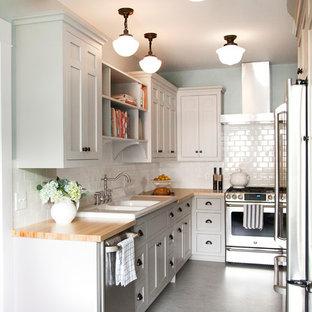 ミネアポリスの小さいトラディショナルスタイルのおしゃれなキッチン (ダブルシンク、落し込みパネル扉のキャビネット、白いキャビネット、木材カウンター、白いキッチンパネル、シルバーの調理設備の、リノリウムの床、アイランドなし) の写真