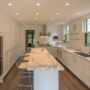 ミネアポリスの大きいトランジショナルスタイルのおしゃれなキッチン (アンダーカウンターシンク、シェーカースタイル扉のキャビネット、白いキャビネット、大理石カウンター、白いキッチンパネル、磁器タイルのキッチンパネル、シルバーの調理設備の、濃色無垢フローリング) の写真