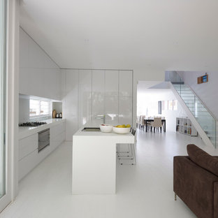Photo of a contemporary l-shaped open plan kitchen in Sydney with a drop-in sink, flat-panel cabinets, white cabinets, panelled appliances, with island and white floor.