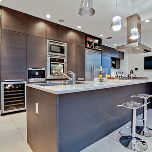 Immagine di una cucina parallela minimalista con ante lisce, ante in legno bruno e elettrodomestici in acciaio inossidabile