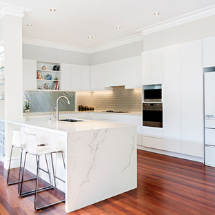 Design ideas for a contemporary u-shaped kitchen in Melbourne with a double-bowl sink, flat-panel cabinets, white cabinets, brown splashback, subway tile splashback, white appliances, medium hardwood floors, a peninsula and red floor.