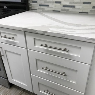 Inspiration for a small modern galley separate kitchen in New York with an undermount sink, shaker cabinets, white cabinets, quartz benchtops, multi-coloured splashback, glass tile splashback, stainless steel appliances, medium hardwood floors, no island, brown floor and white benchtop.
