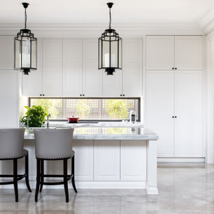 Inspiration for a transitional l-shaped kitchen in Melbourne with raised-panel cabinets, white cabinets, window splashback, stainless steel appliances, with island, grey floor and grey benchtop.
