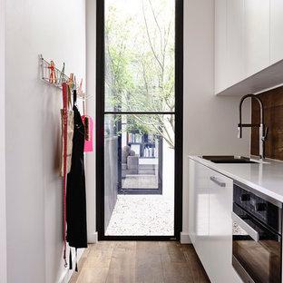 Moderne Küche mit Vorratsschrank, Doppelwaschbecken, flächenbündigen Schrankfronten, weißen Schränken, Marmor-Arbeitsplatte, Rückwand aus Holz, Küchengeräten aus Edelstahl und dunklem Holzboden in Melbourne