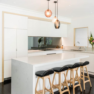 Contemporary l-shaped kitchen in Melbourne with an undermount sink, flat-panel cabinets, white cabinets, metallic splashback, mirror splashback, panelled appliances, painted wood floors, with island, black floor and white benchtop.
