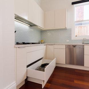 メルボルンの大きいコンテンポラリースタイルのおしゃれなキッチン (ドロップインシンク、フラットパネル扉のキャビネット、白いキャビネット、クオーツストーンカウンター、青いキッチンパネル、サブウェイタイルのキッチンパネル、パネルと同色の調理設備、濃色無垢フローリング、茶色い床、白いキッチンカウンター) の写真