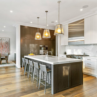 Design ideas for a transitional l-shaped kitchen in Melbourne with a double-bowl sink, shaker cabinets, dark wood cabinets, grey splashback, stainless steel appliances, medium hardwood floors, with island, brown floor and grey benchtop.