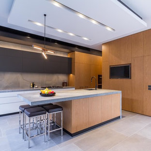 Photo of a large contemporary galley open plan kitchen in Melbourne with an undermount sink, flat-panel cabinets, medium wood cabinets, quartz benchtops, grey splashback, porcelain splashback, black appliances, porcelain floors, with island, grey floor and grey benchtop.