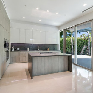 Diseño de cocina en L, moderna, grande, con fregadero encastrado, encimera de piedra caliza, salpicadero negro, salpicadero de piedra caliza, electrodomésticos de acero inoxidable, suelo de mármol, una isla y suelo gris