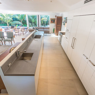 Design ideas for a large midcentury kitchen in Miami with a drop-in sink, flat-panel cabinets, white cabinets, metallic splashback, metal splashback, limestone floors and no island.