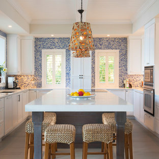 Coastal kitchen remodeling - Example of a beach style u-shaped light wood floor kitchen design in Miami with an undermount sink, shaker cabinets, white cabinets, multicolored backsplash, mosaic tile backsplash, stainless steel appliances, an island and white countertops